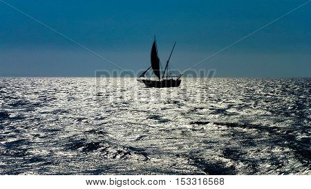 Sailer floating on the silver ocean surface