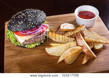 Black burger on the board with fried potatoes; cutlet; vegetables and cheese; with sauce on a wooden board