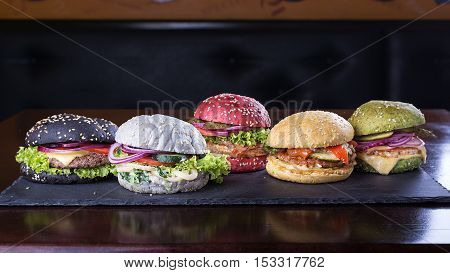 Assorted colored burgers with different fillings with sesame seeds on slate blackboard