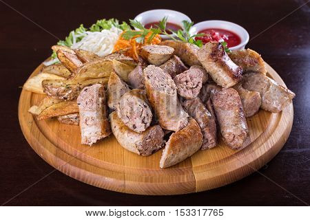 Assorted sliced sausage on a wooden board with potatoes cabbage and carrots in Korean with tomato sauce and the sauce adjika
