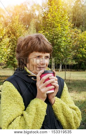 Mature woman in the park holding to go coffee cup. Attractive smiling elderly woman with cup of coffee, sitting alone in public park. Old woman walkin in the park with coffee to go.