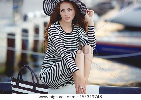 Beautiful young woman model looks,brunette with long curly hair and blue eyes,on his head wearing striped straw hat with a large brim,dressed in a striped summer dress,spends time on the ocean, close to Parking of boats and yachts