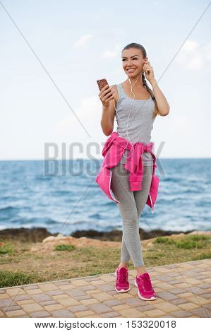 Young beautiful woman with athletic build,brunette with hair gathered at the back,light makeup,wearing a gray shirt and gray sweat pants,tied at the waist sports jacket pink,listening to music with headphones standing on beach