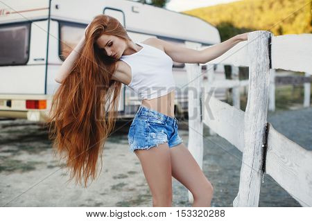 Portrait of sexy redheaded woman,long thick hair,freckles on face,big lashes and beautiful eyebrows,dressed in a short white shirt and blue shorts,a beautiful slender figure,posing outdoors in the summer in the countryside on a country ranch
