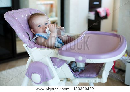 A little kid with fluffy blond hair and blue eyes,dressed in a blue t-shirt,sits alone at the lilac table for feeding babies,in the hands holding a feeding bottle filled with water