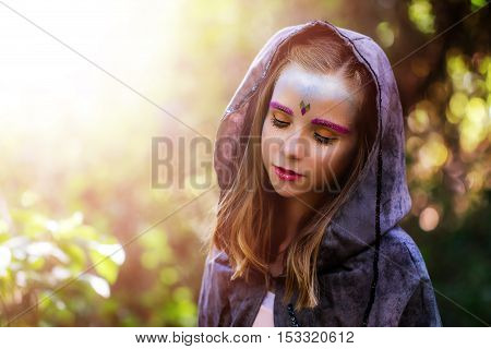 Close up beauty portrait of mysterious little girl wearing dark costume in woods.Kid with fantasy make up standing against sunlight with eyes closed.