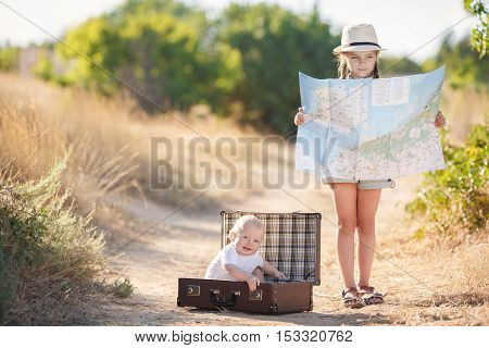 Little boy in a white t-shirt is resting sitting in a large open brown suitcase on a country road, the elder sister is studying map of the area, a girl 6 years old in a gray summer suit with long braids, in a light hat and a beige backpack