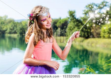 Conceptual beauty portrait of little girl dressed up as little princess. Girl casting spell with magic wand next to lake.