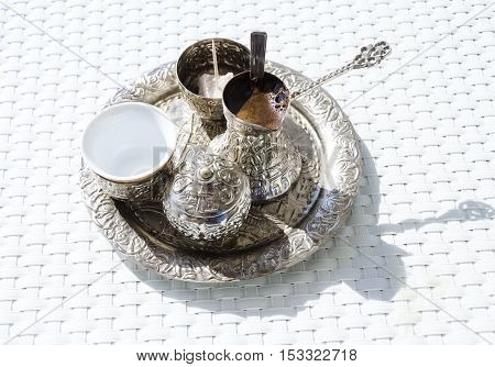 A metallic tray with copper plated cezve (d?ezva) filled with traditional foam Bosnian coffee a silver pot with turkish delight rahat lokum a clay cup and sugar cube pot served in an ornament Sarajevo set. poster
