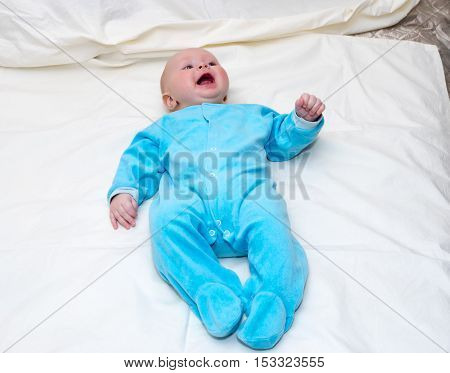 Four month old baby smiling while lying on the bed