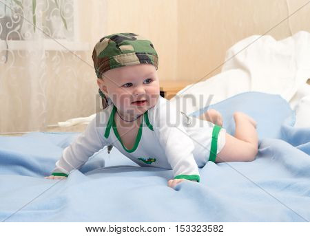 Kid in the camouflage bandana plays lying on his stomach