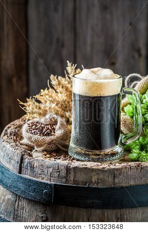 Fresh Pint Of Dark Beer, Hops And Wheat On Old Barrel