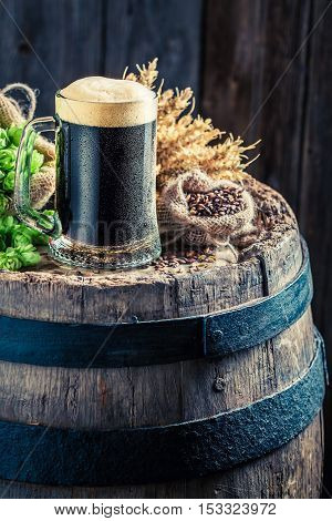 Fresh And Cold Dark Beer On Wooden Barrel With Hops And Wheat