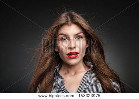 Confused woman got really surprised. Studio portrait on black vignette background.