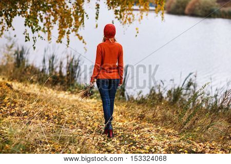 Lonely woman walking away in the autumn park