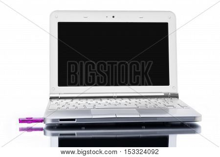 open silver netbook and pink USB key with reflected shadow isolated