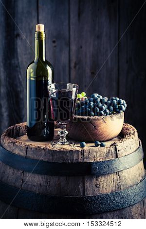 Delicious Red Wine With Fresh Grapes On Wooden Barrel