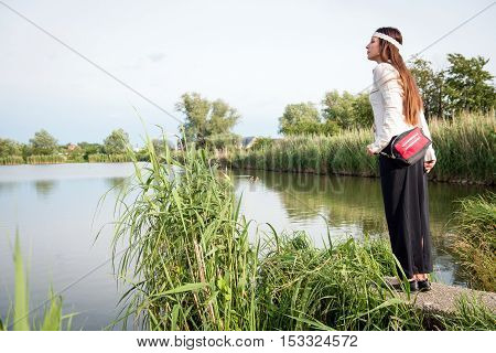 Portrait of young hippie lady with handbag standing by the lake