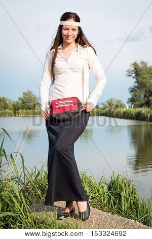 Portrait of young hippie lady with handbag posing by the lake