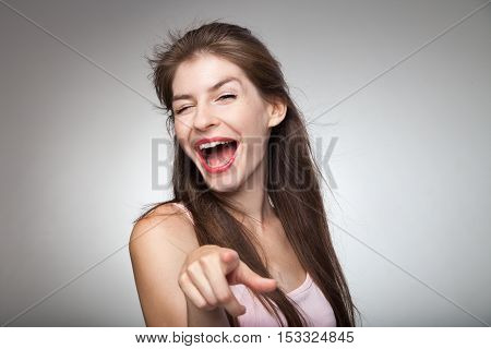 Flirtatious girl pointing on camera and winking. Studio portrait.