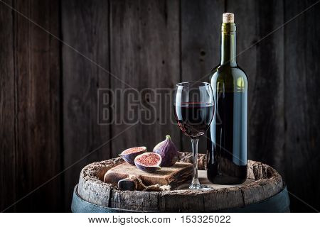 Fresh wine in glass with figs on old wooden barrel