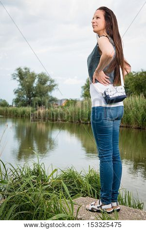 Portrait of young lady in jeans with handbag standing by the lake