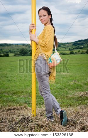 Portrait of young lady with handbag posing by the yellow pole
