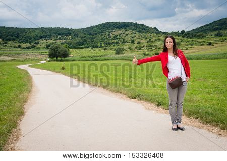 Portrait of young lady in red jacket hitchhiking by the road