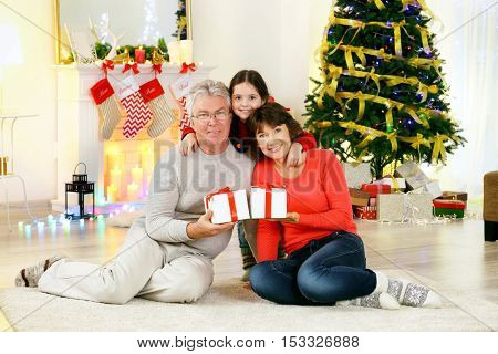 Little girl and her grandparents in living room decorated for Christmas