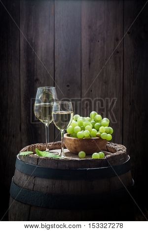 Tasty White Wine In Glass With Grapes On Old Barrel