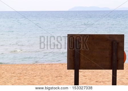 one big wooden billboard is established on the sandy beach and a view from a reverse side