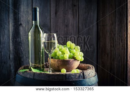 Fresh White Wine With Grapes On Old Barrel