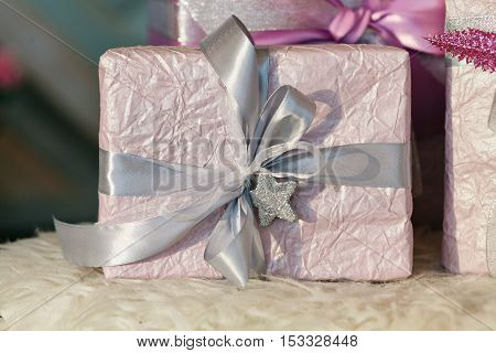 Holiday gift boxes decorated with ribbon. Beautiful purple shiny package for Christmas and New Year. Sebebryannaya tape. Background with copy space for entering text.