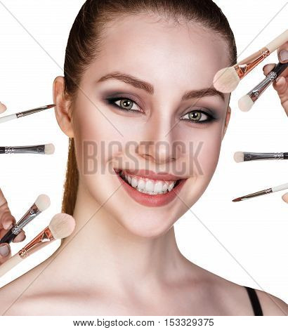 Portrait of beautiful young woman with makeup brushes isolated on white