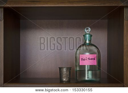 Glass bottle with poison and metal glass stand on a shelf