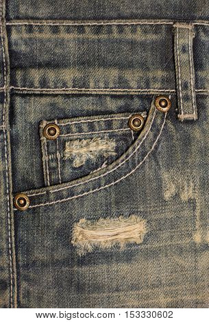 Old dirty blue jeans with holes and scrapes. Jeans pocket with bronze buttons. Rivets with sign JEANS in rim.