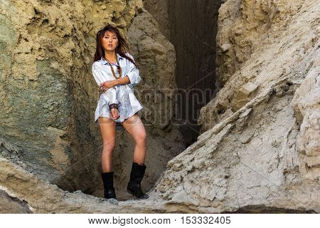 Asian girl shaman at the entrance to the cave