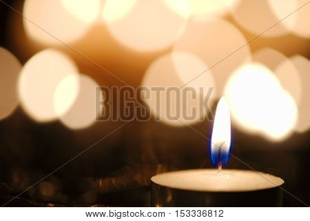 Blue candle flame against defocused golden candlelight background