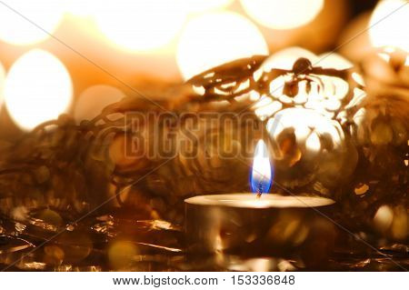 Burning candle against Christmas decoration and candlelight background