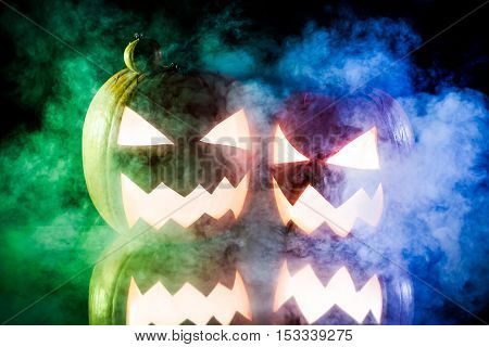 Two Pumpkins For Halloween On Blue And Green Smoke