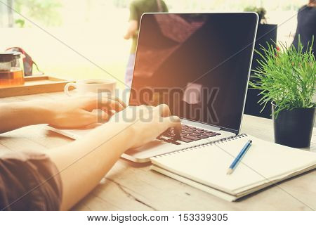 Man hand use laptop working with notebook vintage tone.