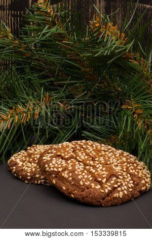 Cookies with sesame seeds and fir branch on a dark background
