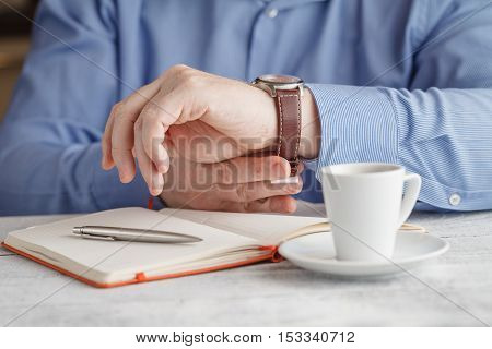 Close-up image of a man drinking tasty espresso coffee on the foreground poster