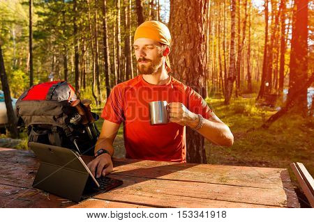 Young, successful, bearded man, sitting at table by the river and is working on tablet, outdoors