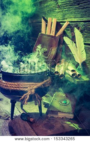 Old Witcher Cauldron With Green Smoke And Books For Halloween