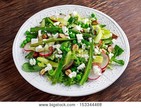 Fresh Green Asparagus salad witch Goat Cheese, peas, radishe, zucchini, lettuce and Hazelnuts