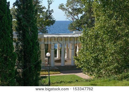 Portico of old pavilion of Doric order among trees in park on seaside.