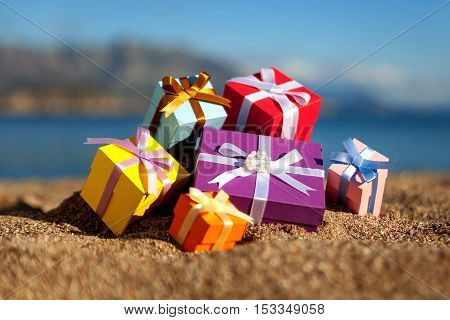 Group of multicolored gift boxes on a beach