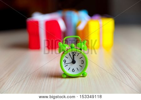 Group of multicolored boxes and alarm clock on a wooden background