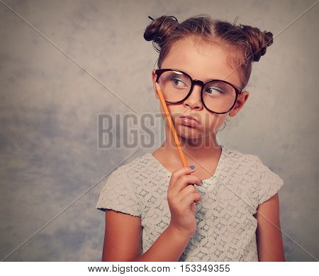 Thinking Grimacing Kid Girl In Glasses Looking And Holding Pencil In Hand On Blue Background With Em
